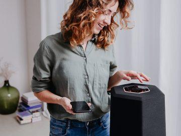 Junge Frau bedient Smart Speaker.