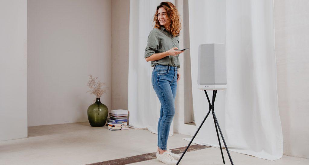 Lachende Frau neben Smart Speaker HOLIST M auf Gestell