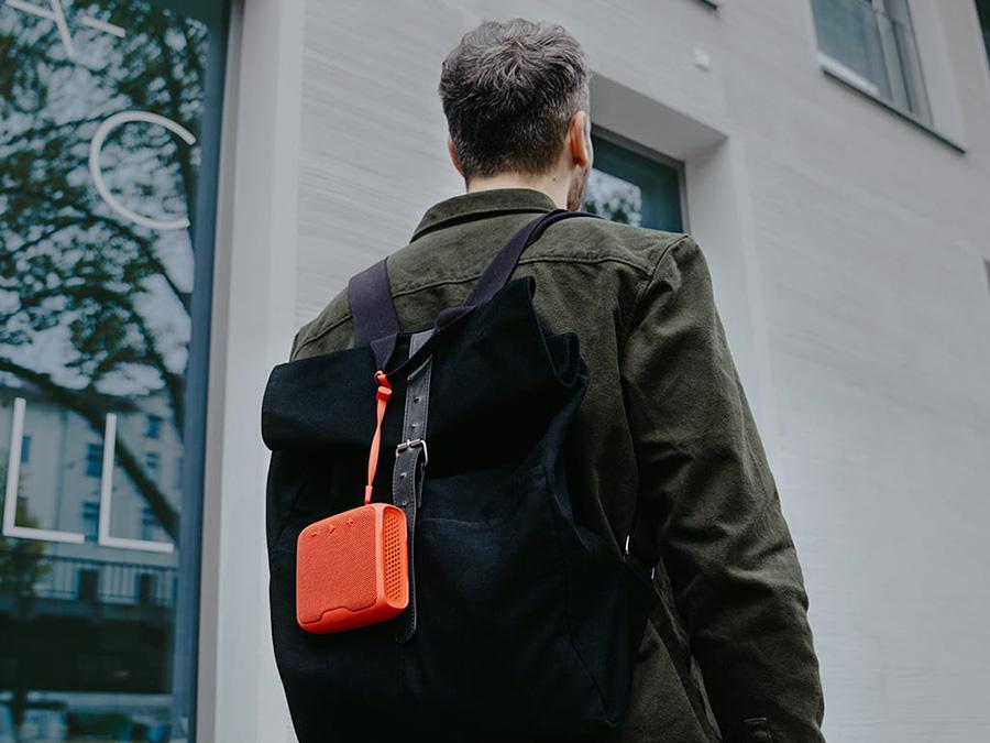 Rückenansicht Mann mit Rucksack und BOOMSTER GO in Orange