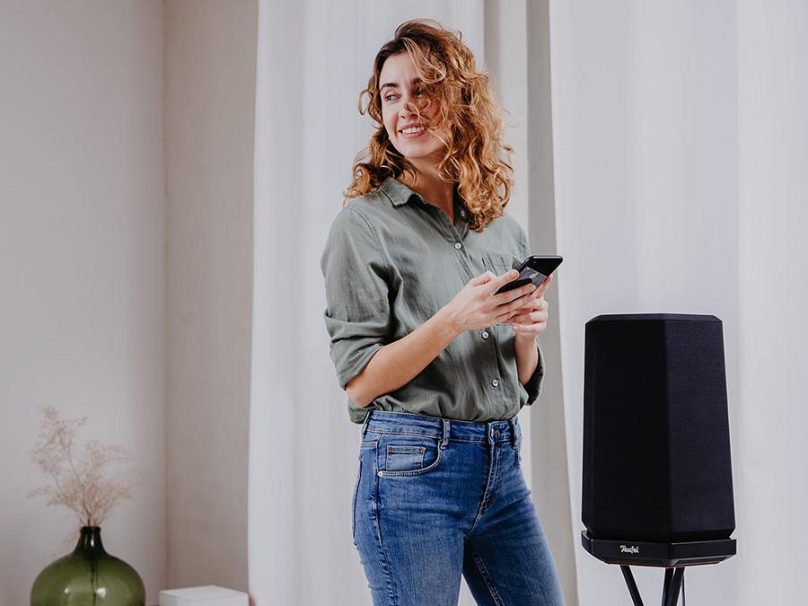 Lachende Frau mit Handy neben Lautsprecher HOLIST M