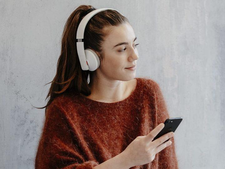 Junge Frau mit Kopfhörer und Smartphone.