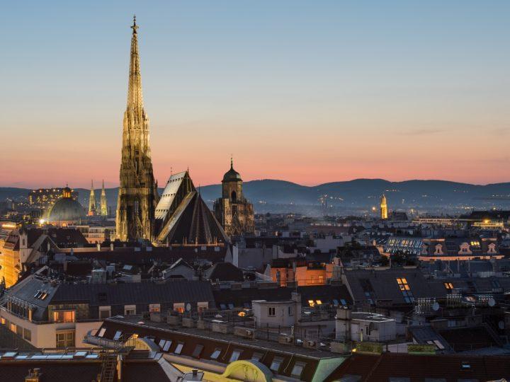 Blick von oben auf die Stadtsilhouette Wiens nach Sonnenuntergang.