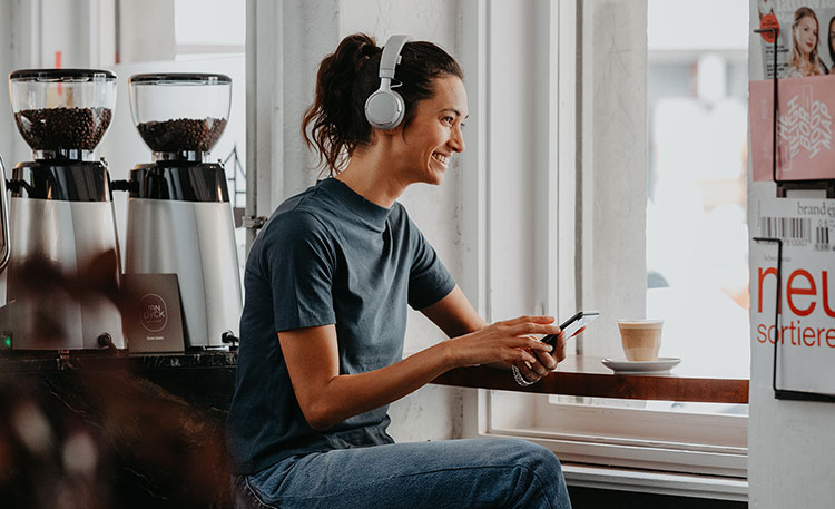 Lachende Frau in Café mit Kopfhörer SUPREME ON und Smartphone