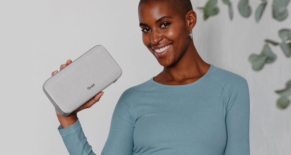 Lachende Frau mit grauem Lautsprecher MOTIV GO in der Hand