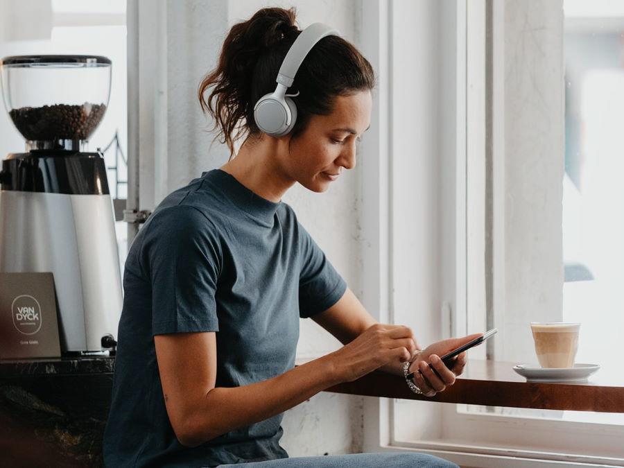 Frau mit Kopfhörer SUPREME ON und Handy