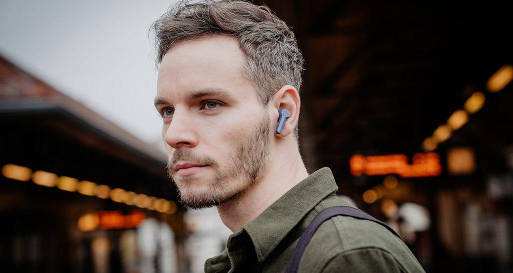 Mann trägt unterwegs kabellose In-Ear-Kopfhörer