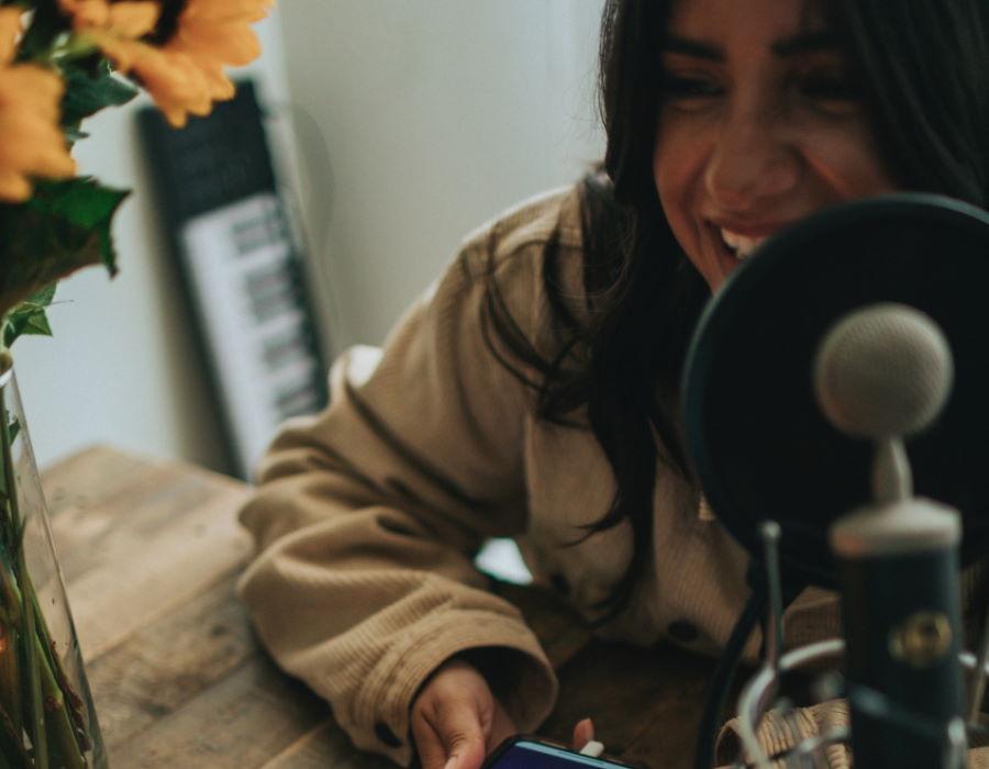 Lachende Frau vor Mikrofon