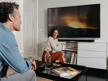 Mann auf Sofa und Frau vor Soundbar und Fernseher