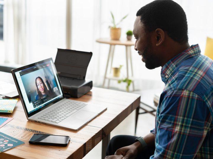 Mann im Video-Call vor Laptop